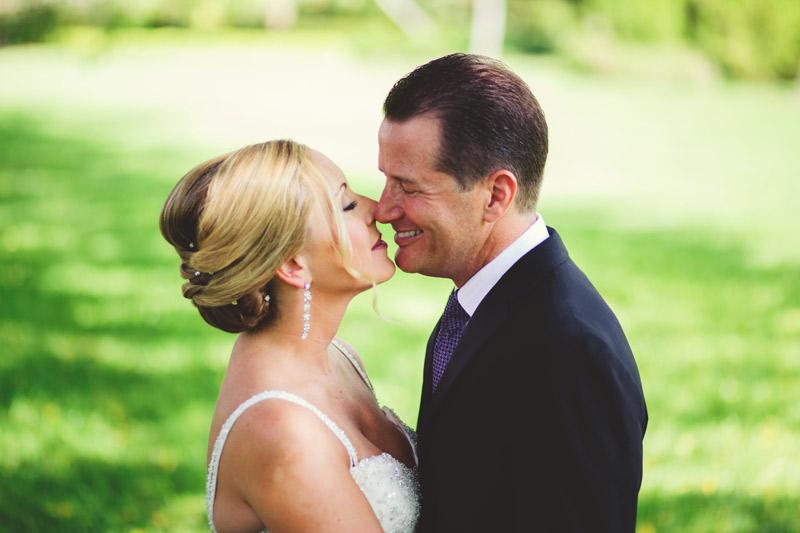 naples backyard beach wedding: bride and groom kissing under banyan tree