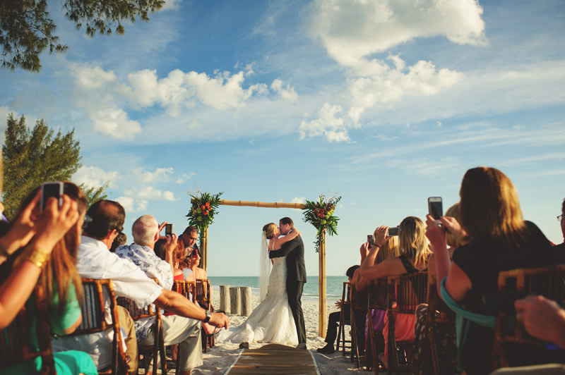 naples backyard beach wedding: bride and groom kiss