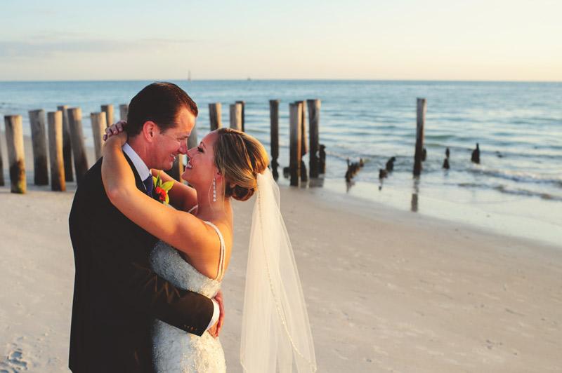naples backyard beach wedding: bride and groom hugging on beach