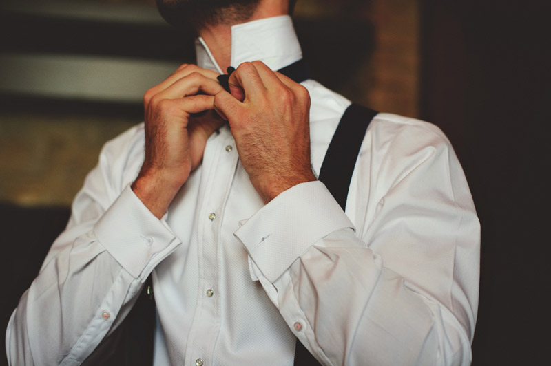 bella collina wedding: groom putting on bow tie