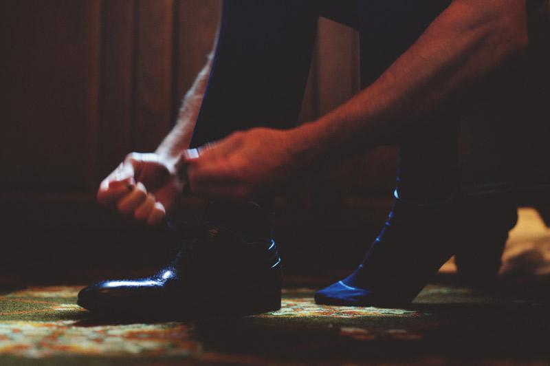 bella collina wedding: groom tying shoes
