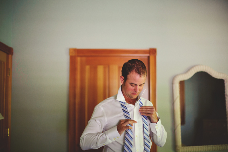 caribbean resort wedding: groom putting on tie