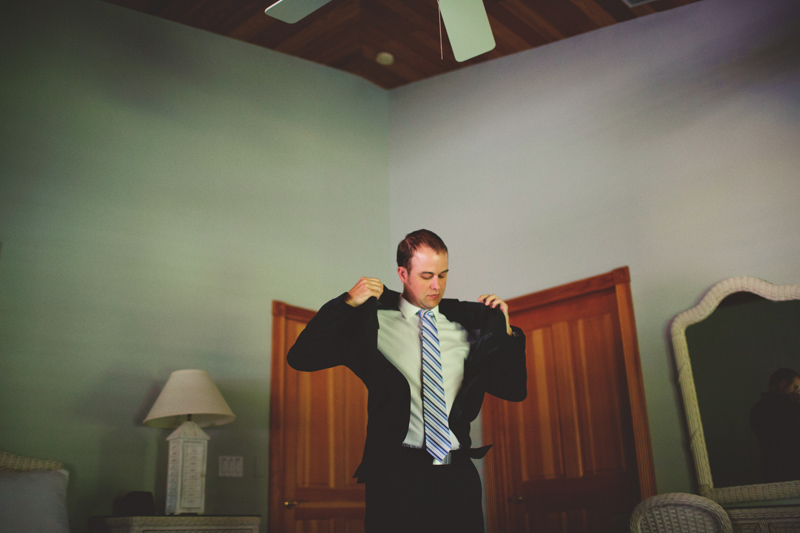 caribbean resort wedding: groom putting on jacket