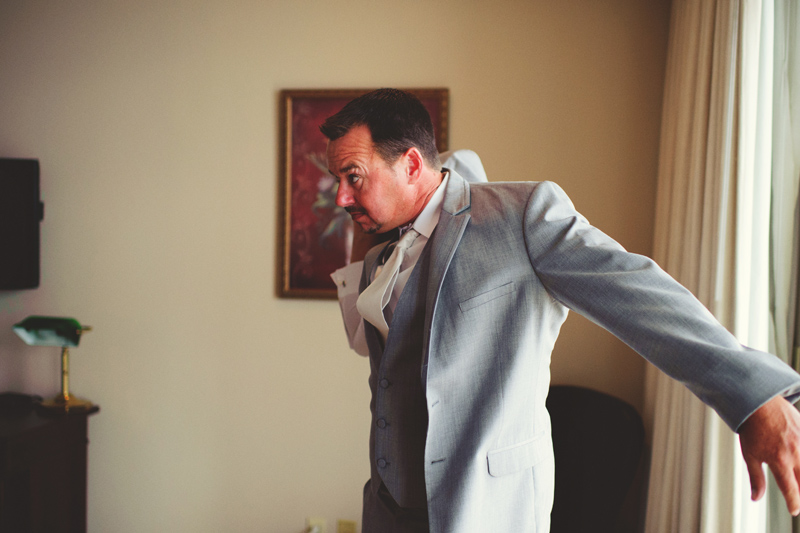 the club continental wedding: groom putting on jacket