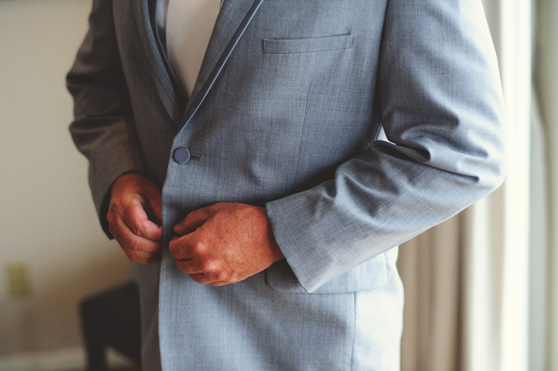 the club continental wedding: groom buttoning jacket