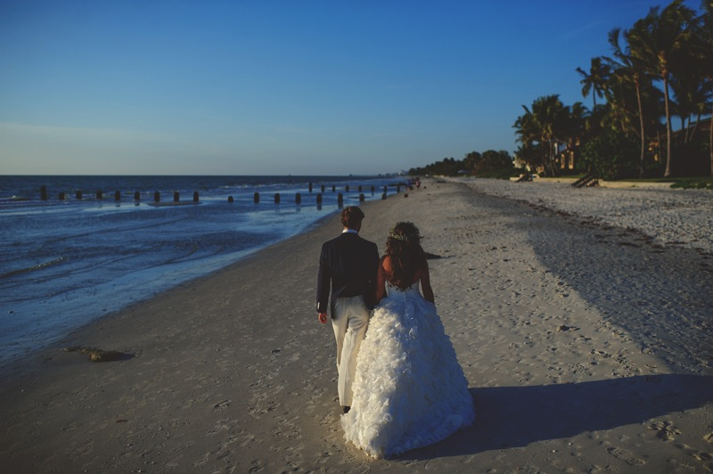 boho backyard wedding naples: bride and groom walking on beach