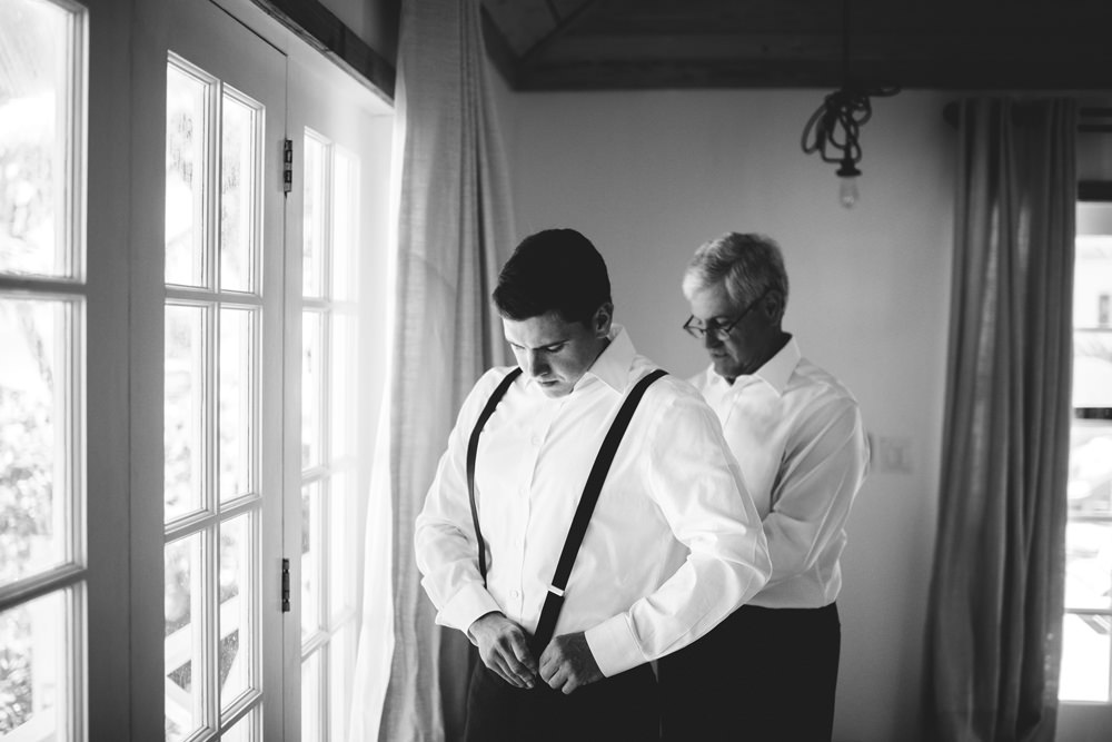ocean view club wedding : groom putting on suspenders