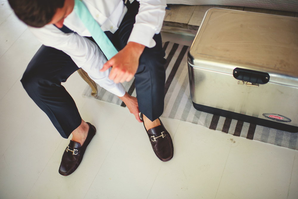 ocean view club wedding : groom putting on shoes