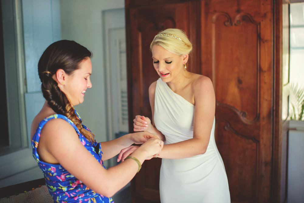 ocean view club wedding : bridesmaid helping with bracelet