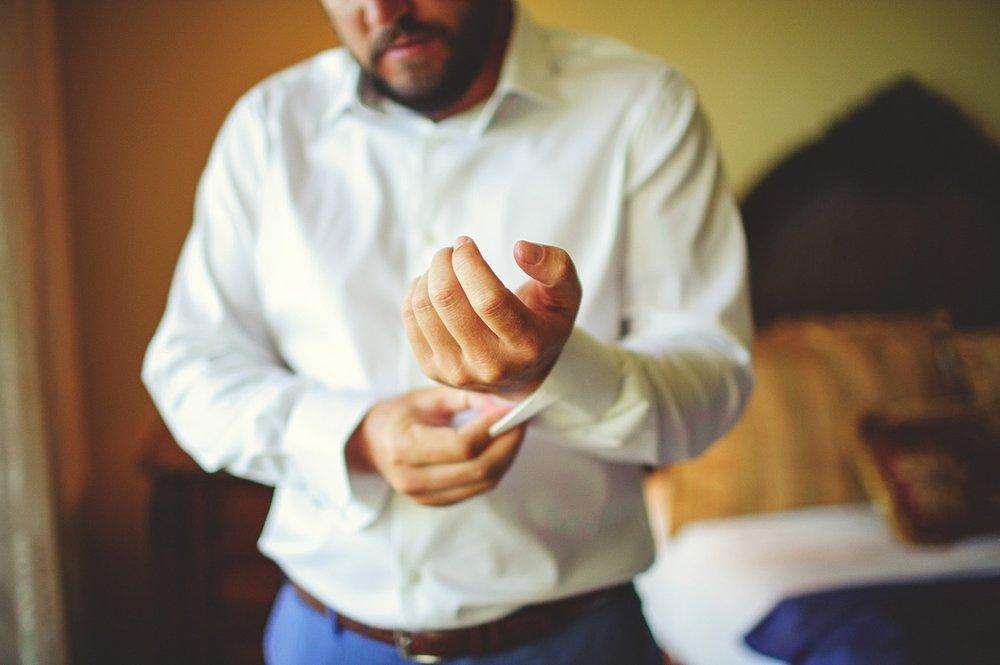 pierre's restaurant wedding: groom putting on cufflinks