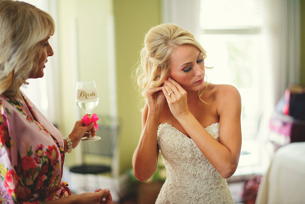 Harper Fowlkes House wedding: bride putting in earrings