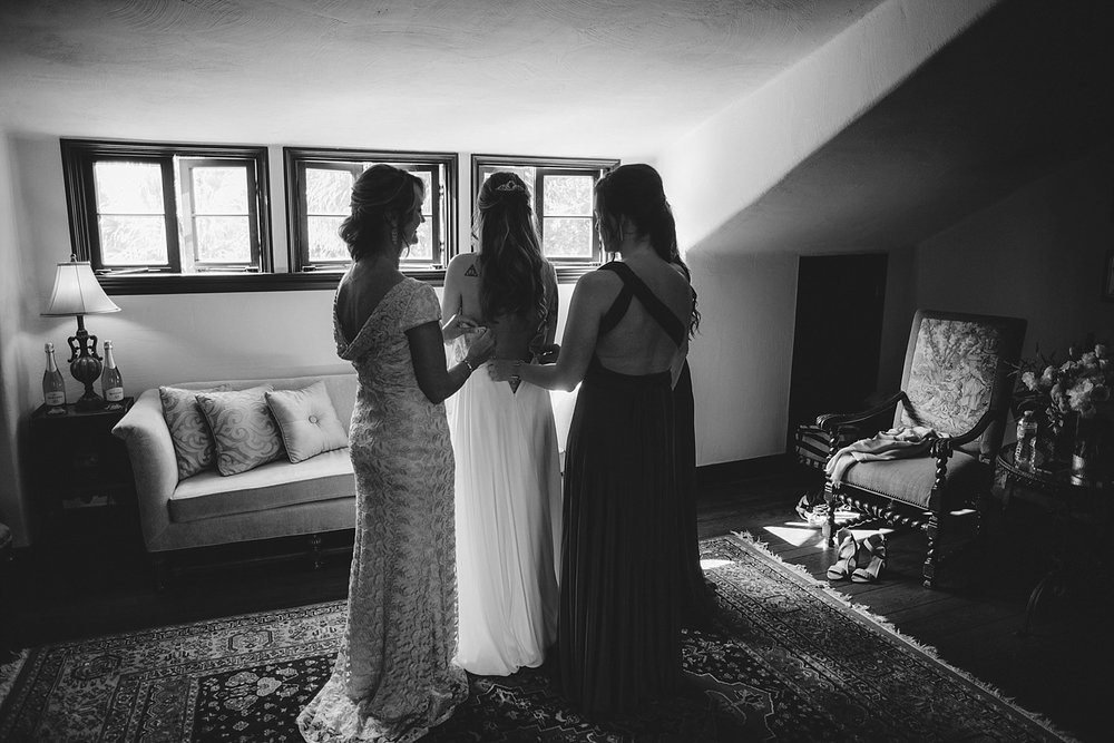 casa feliz wedding photos: bride putting on wedding dress