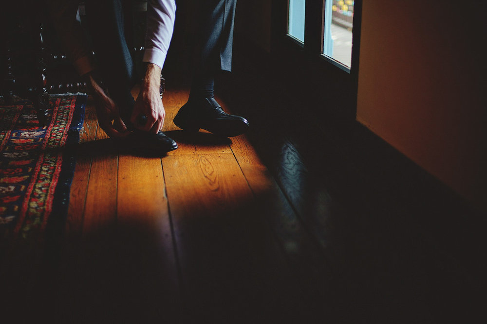 casa feliz wedding photos: groom putting on shoes