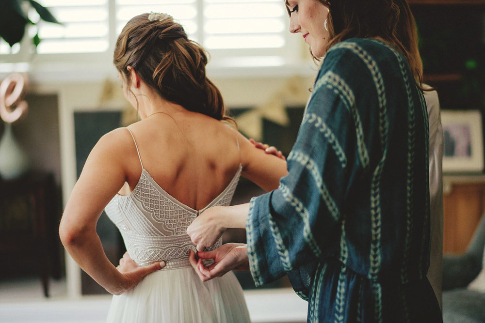 knowles memorial chapel wedding: maid of honor zipping up weddin