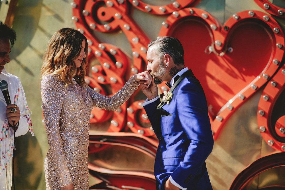 neon museum wedding - groom kissing hand