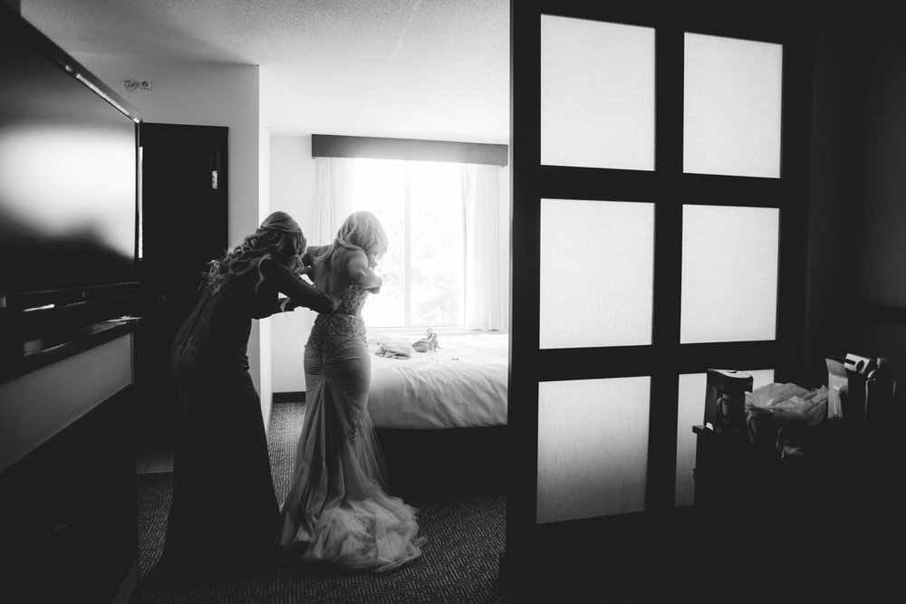 editorial ringling wedding: bride getting into wedding dress