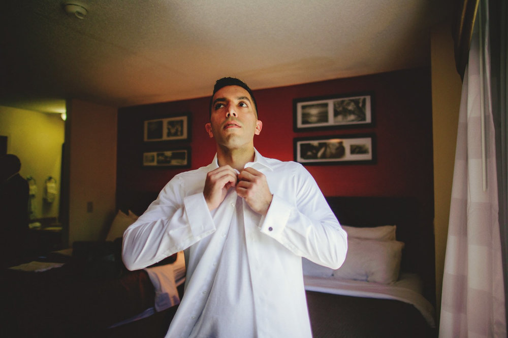 editorial ringling wedding: groom putting on shirt