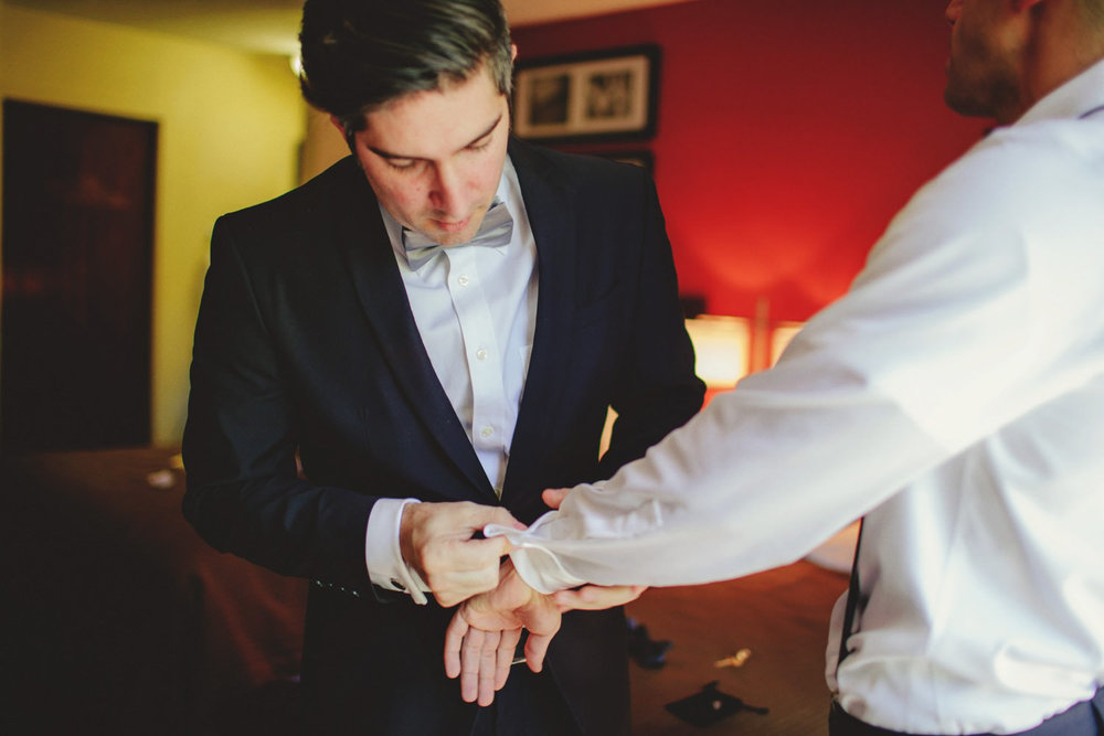 editorial ringling wedding: best man helping with cufflinks