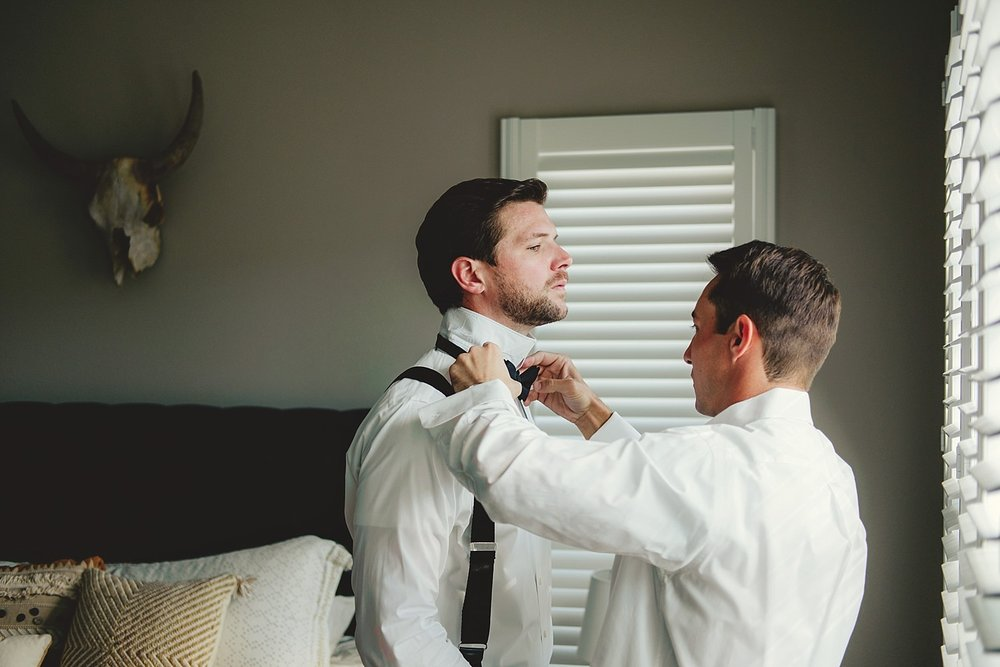 best man helping with bow tie