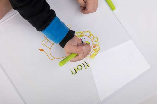 Tracing the word and drawing of a lion onto a piece of acrylic.
