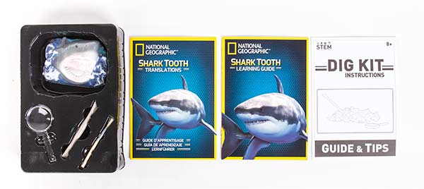 Contents of the National Geographic Shark Tooth Dig Kit: Encased Shark Teeth, tools, magnifying glass, learning guides and instructions.