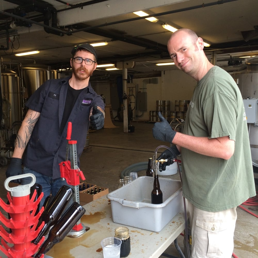 Head Brewer Sean Lewis (right) and brewer EZ package Flat12's barrel aged beers in limited 22 oz. bombers