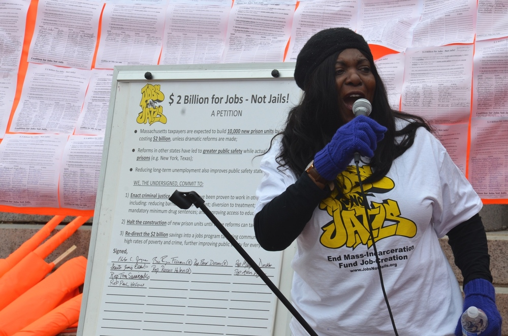 Executive Director of  EPOCA  Cassandra Bensahih rallying the crowds at a Jobs NOT Jails action at the Massachusetts Statehouse, 2014
