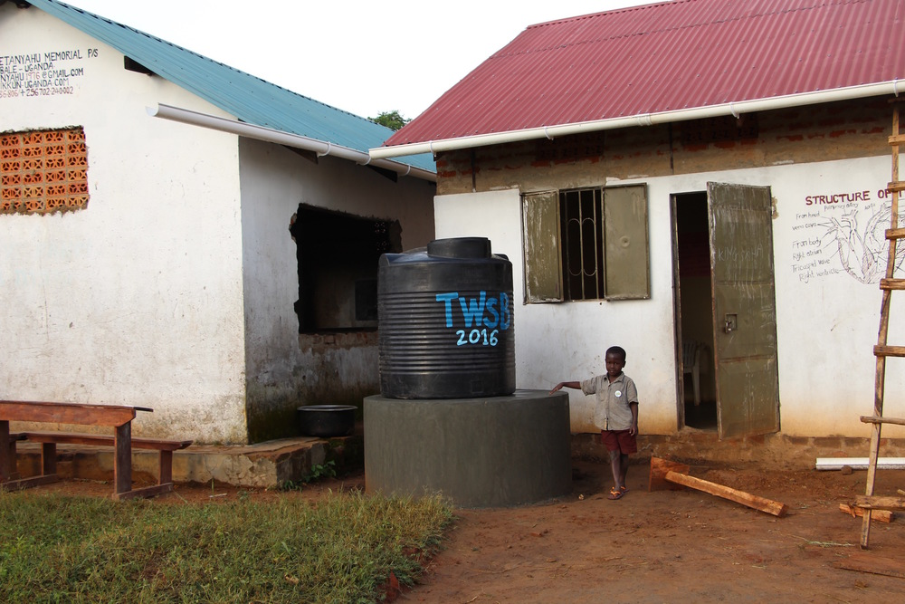 Young JJ Keki (Enosh's Son) standing in front of the new water catchment system which is the first of its kind in Putti Village. Here, rain is captured in the gutter systems and channeled down into the 1000L storage tank. From there, it is stored to water the garden and to provide drinking water when the bore hold has dried up.