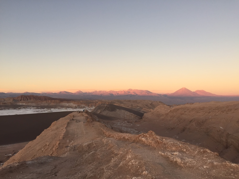 The last rays of sunlight on Valle de la Luna. The human specks on the ridge offer a sense of how grand this place is.