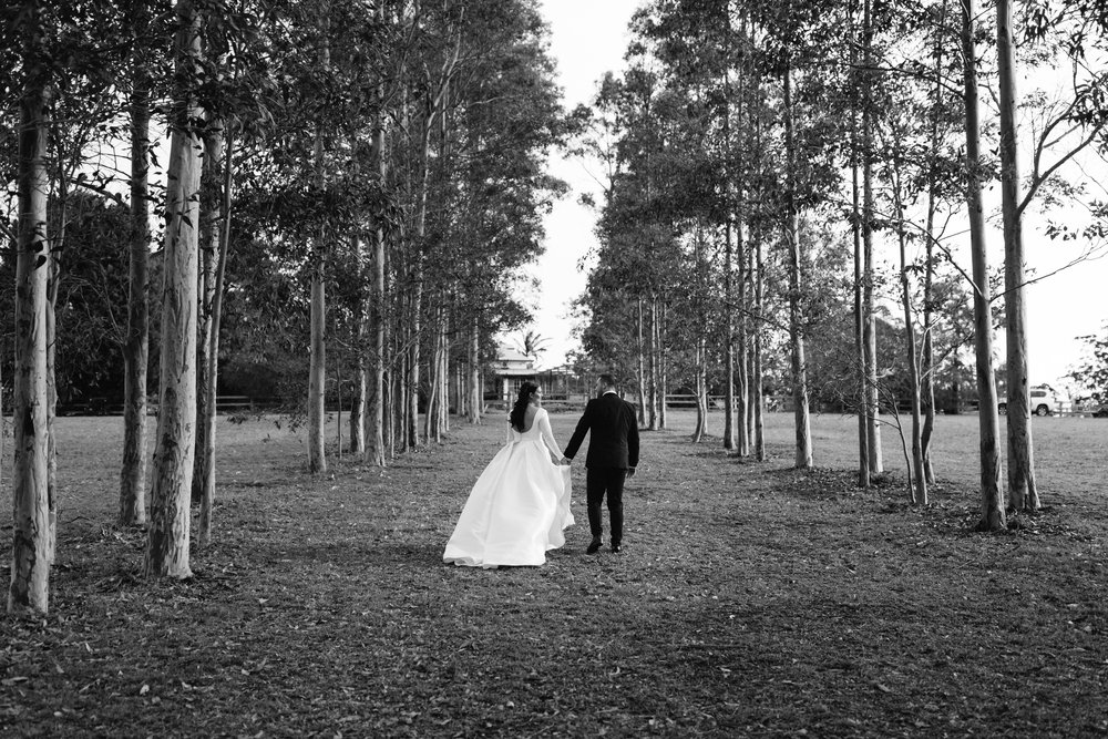 Black and white photo of bride and groom holding hands walking through trees at Worrowong Estate Jervis bay by Blue Mountains wedding photographer Joshua Witheford