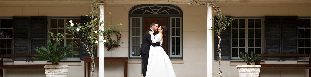 Bride and groom at kissing on steps of house at worowing estate Jervis bay by Blue Mountains wedding photographer Joshua Witheford