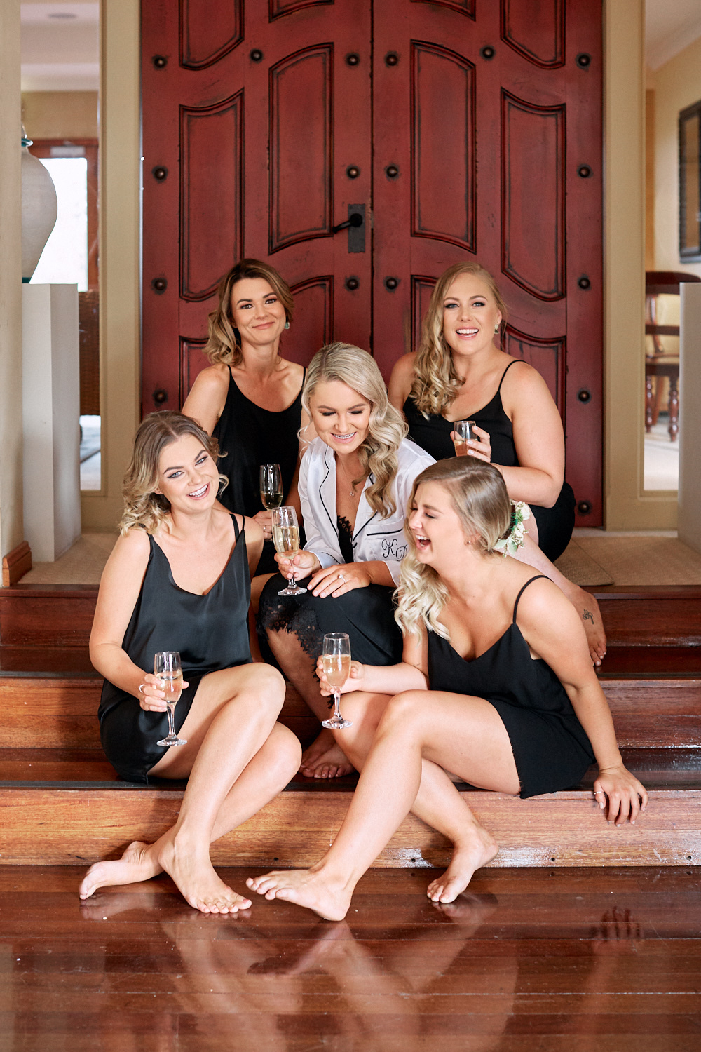 Bridesmaids drinking champagne and laughing on steps at Estate Tuscany Pokolbin in the Hunter Valley by wedding photographer Joshua Witheford