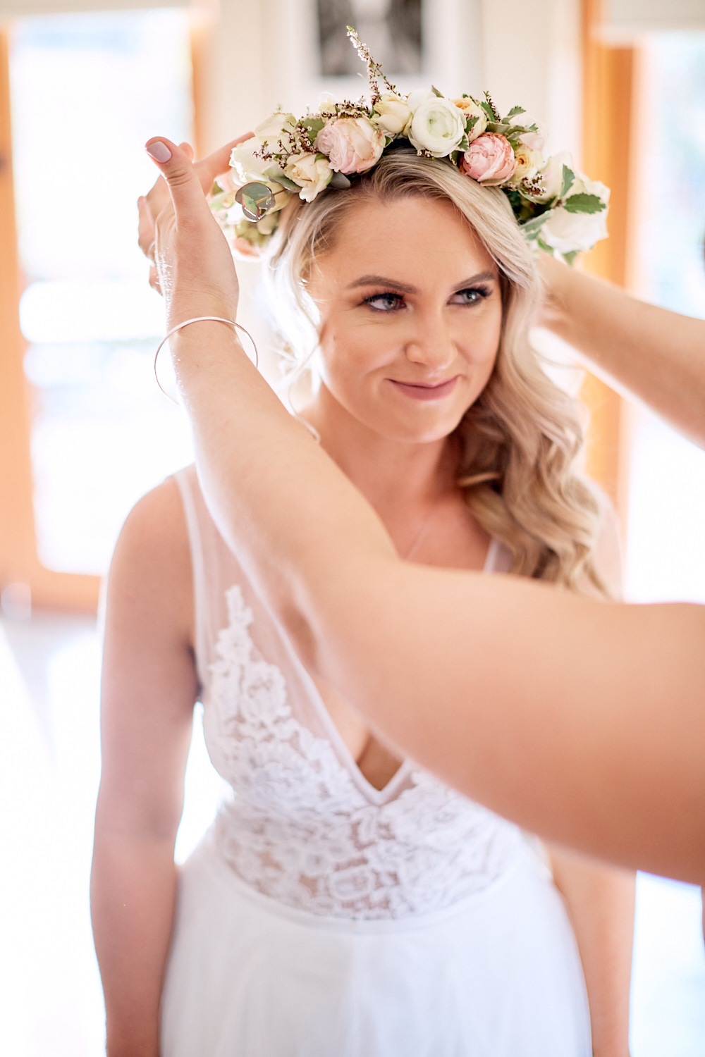 Bride putting on flower crown in her wedding dress at Estate Tuscany Pokolbin in the Hunter Valley by wedding photographer Joshua Witheford