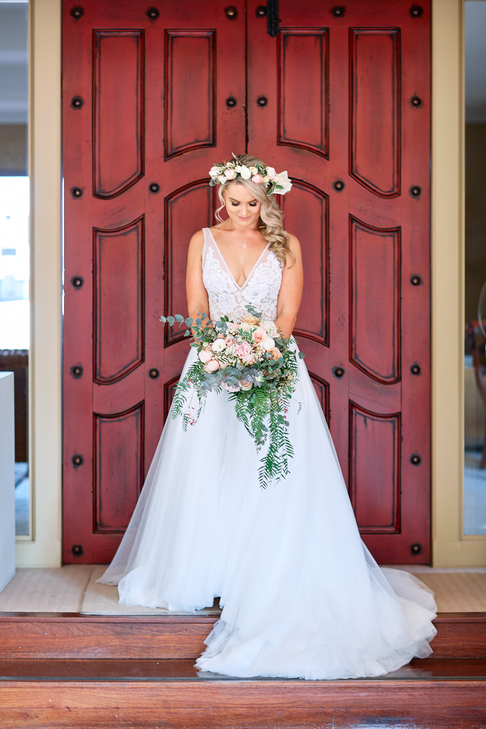 Bride wearing wedding dress in front of red door at Estate Tuscany Pokolbin in the Hunter Valley by wedding photographer Joshua Witheford