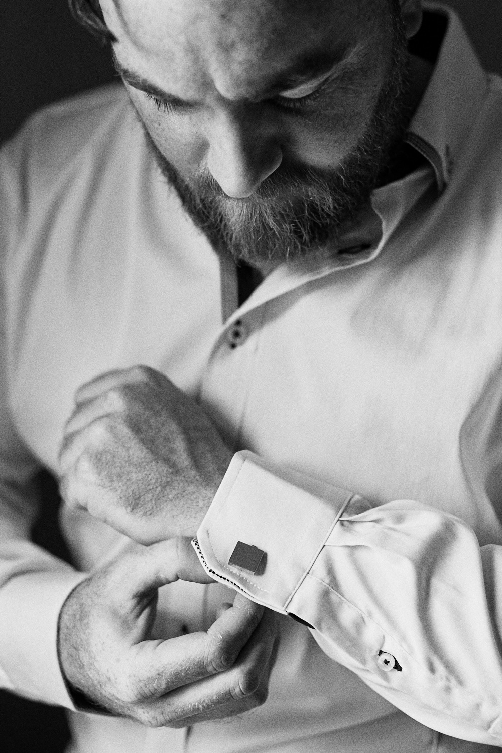 Black and white photo of groom putting on cufflinks at Estate Tuscany Pokolbin in the Hunter Valley by wedding photographer Joshua Witheford