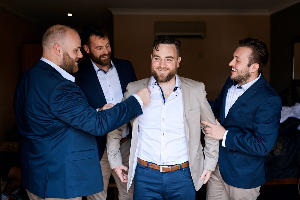 Groomsmen dressing groom at Estate Tuscany Pokolbin in the Hunter Valley by wedding photographer Joshua Witheford