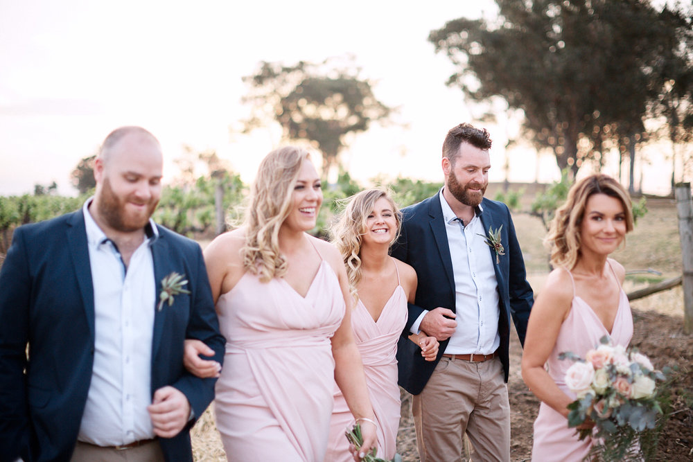 Bridal party walking through vineyard at Estate Tuscany Pokolbin in the Hunter Valley by wedding photographer Joshua Witheford