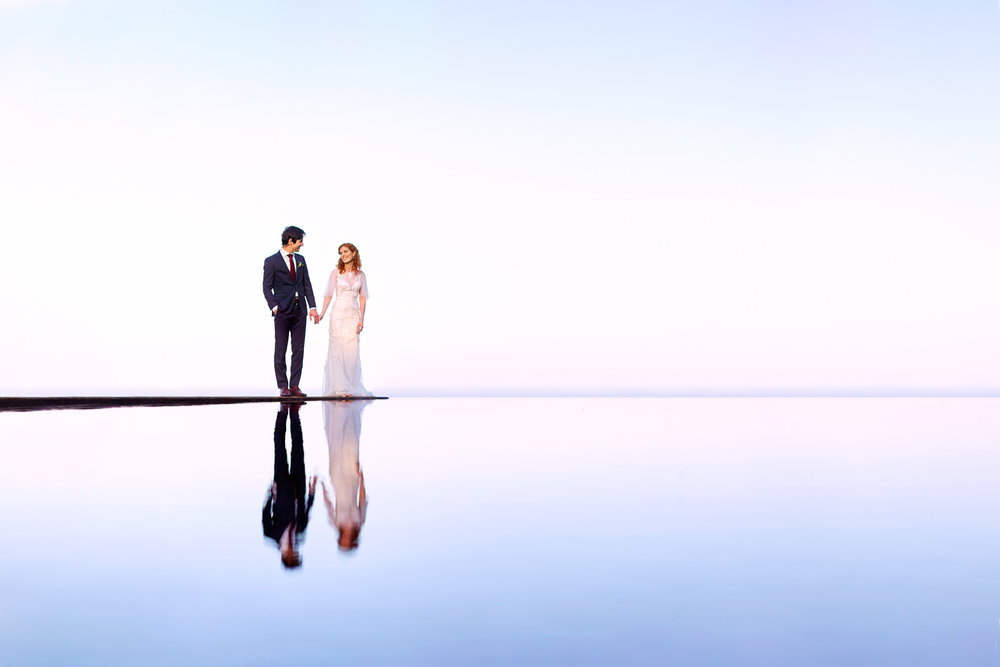 Newlyweds holding hands reflecting in water at sunset