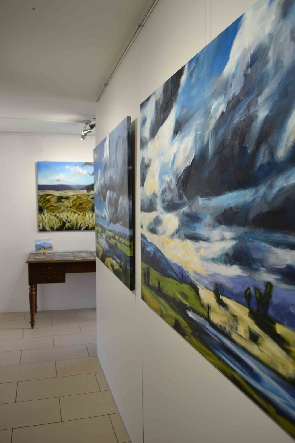 Big Australian Skies. Installation photo of the current exhibition. Images left to right. 1/ Towards Drayton's Vineyard, oil on cotton canvas, 86 x 116cm 2/On the table, various en plein air oil paintings from Italy. 3/ Gilleston Island (after the flood), oil on cotton, 86 x 115cm. 4/ Evening Light on Teddy's Hill, oil on cotton, 86 x 115cm.