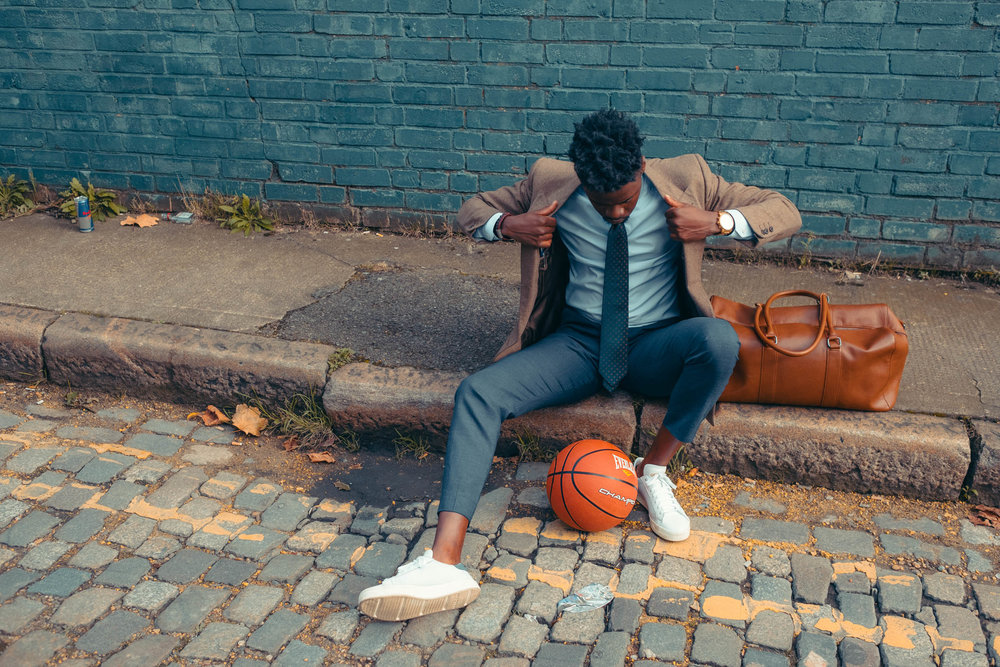 Javanandre-adjusts-suit-whilst-sat-roadside-with-holdall-and-bas