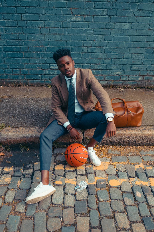 Javanandre-sat-roadside--wearing-suit-with-holdall-and-basketbal