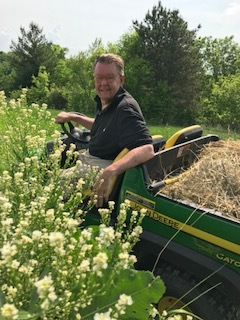 "John really enjoys his 'gator,' riding around the property and checking on the different plantings.  This weekend the horseradish was in bloom. What an interesting plant…a member of the Brassicaceae family and a relative to plants such as mustard, broccoli, kale, and radishes. It is cultivated for its thick, fleshy white roots.  The ""hotness"" from horseradish comes from isothiocyanate, a volatile compound that, when oxidized by air and saliva, generates the ""heat"" that some people claim clears out their sinuses. The bite and aroma of the horseradish root are almost absent until it is grated or ground. During this process, as the root cells are crushed, isothiocyanates are released. Vinegar stops this reaction and stabilizes the flavor. For milder horseradish, vinegar is added   immediately .     (horseradish.org)"