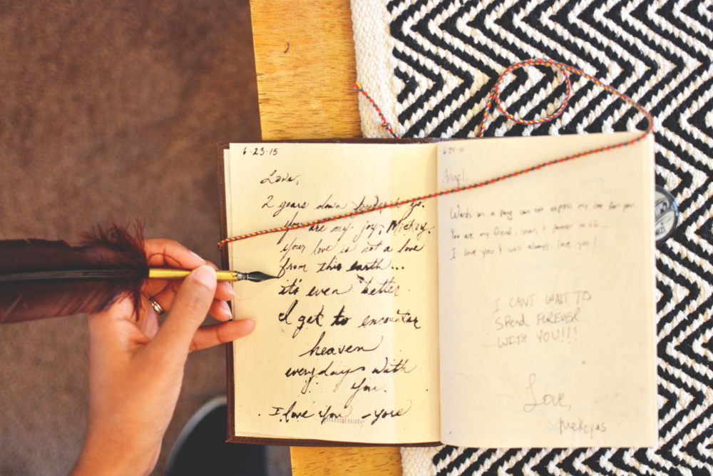 [image: Pictured from above -A person holds a quill in their left hand above an open journal. The journal is atop a black and white patterned cloth on a table.