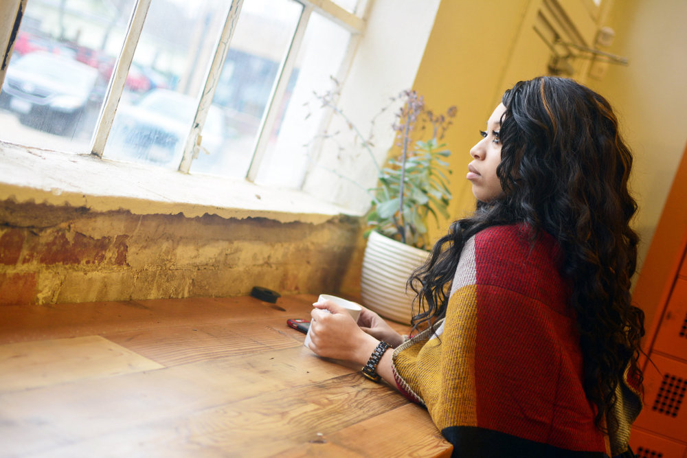 [Pictured: a woman with long, wavy black hair and a multi-colored shawl stares out of a window while holding a coffee cup.]