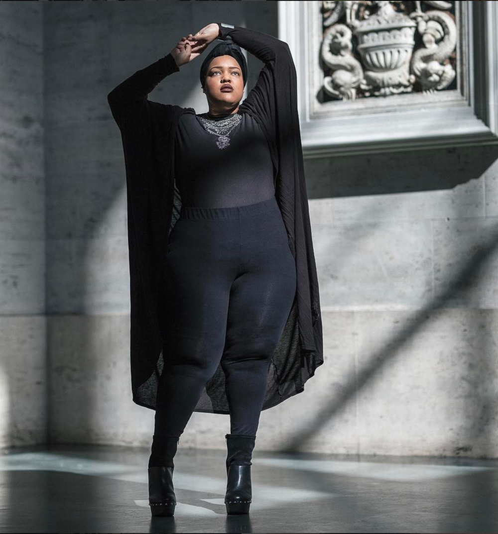 [Image Description: photo showing Leah standing in all black against a stone grey background. She is wearing a black hijab, black leggings, black shirt, black wrap and a silver necklace. Her arms are raised above her head]