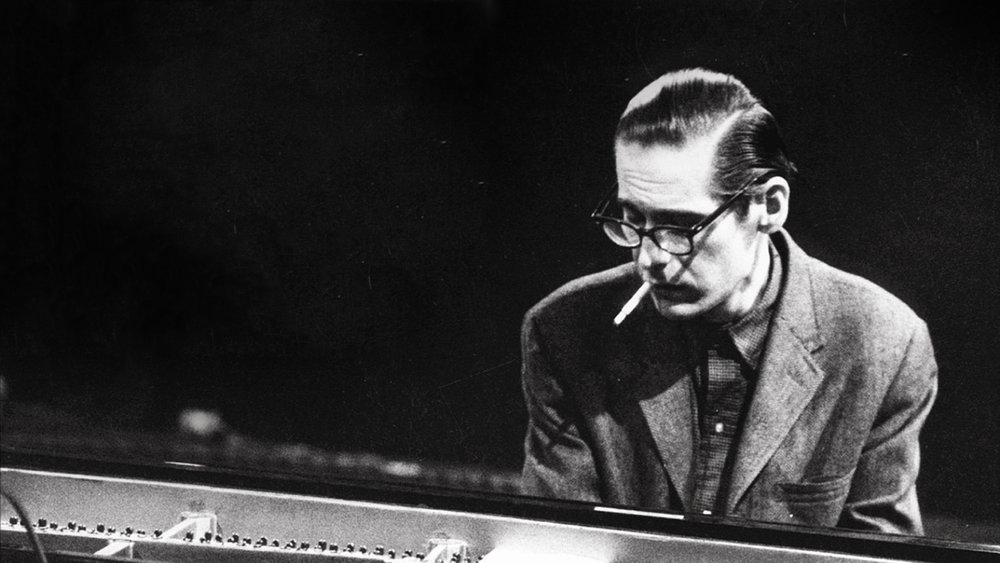 Bill Evans (Image Description: Pianist Bill Evans sits at the keyboard with a cigarette in his mouth. )
