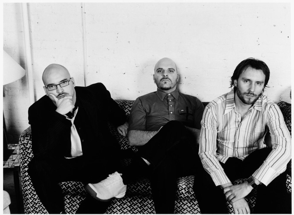 The Bad Plus (Image Description: Three men sit on a patterned couch looking directly into the camera)