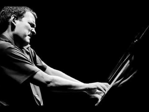 Brad Mehldau (Image Description: Man sits at piano keyboard and plays wth intensity.)