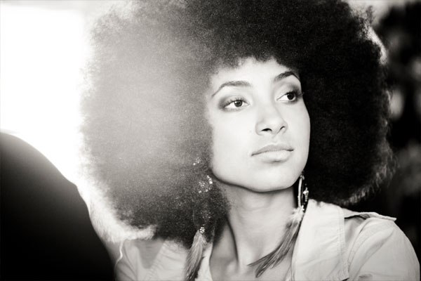 Esperanza Spalding (Image Description: Woman with an afro, wearing hoop earring looks into the distance)