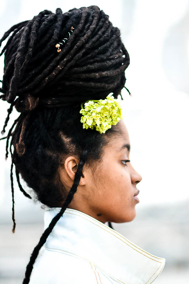 A woman with a flower in her dreadlocked hair looks of into the distance.